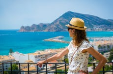 Female traveler gazes out over scenic seascape from balcony