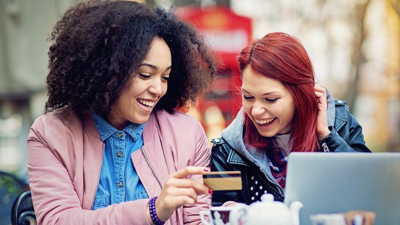 Two girlfriends are shopping online in the cafeteria