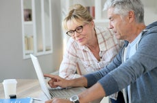 Older couple discuss information on laptop