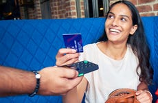 Young woman hands credit card to restaurant merchant