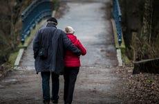 An older couple walks toward a bridge