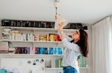 Woman replaces a lightbulb in her home