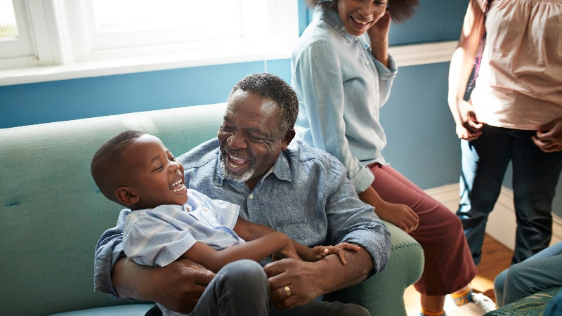 An African-American family and child laugh on a couch