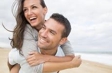 A young white couple walk along a sandy white beach
