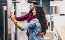 couple looking at refrigerators in store