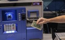 A man gets money from an ATM.