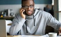 A man at home makes a phone call.