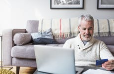Man using credit card and laptop while shopping online at home