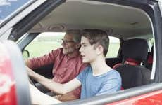 Father teaching son driving a car