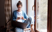 woman sitting at home looking at phone with laptop