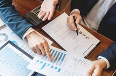 Two advisers analyzing financial sheets