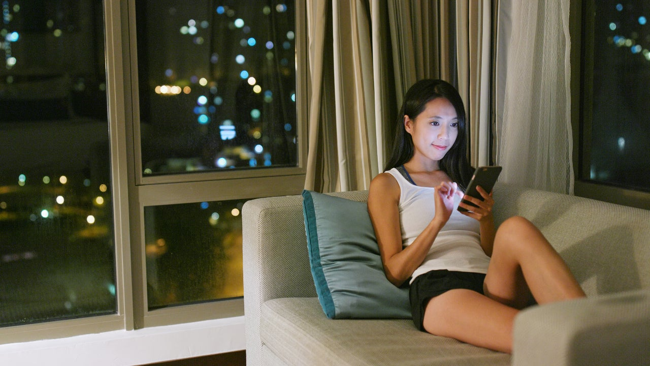 A woman sits on a couch and uses her mobile phone.