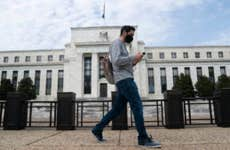 A man wearing a mask walks past the U.S. Federal Reserve building in Washington D.C.