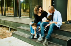 family sitting on front porch of home
