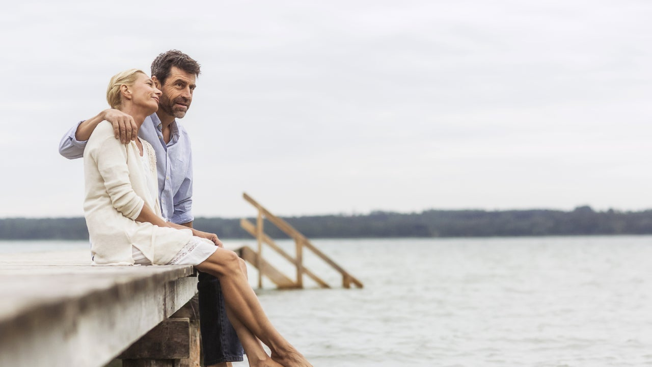 Older couple sitting together on a dock over a lake.