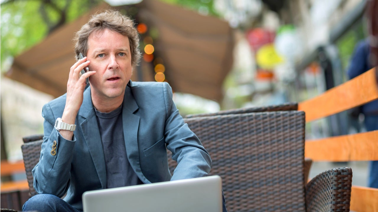 Businessman talking on phone outside.