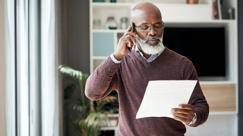 An older African-American man talks on the phone in his home