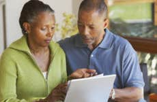 A senior, African-American couple look at a laptop together.