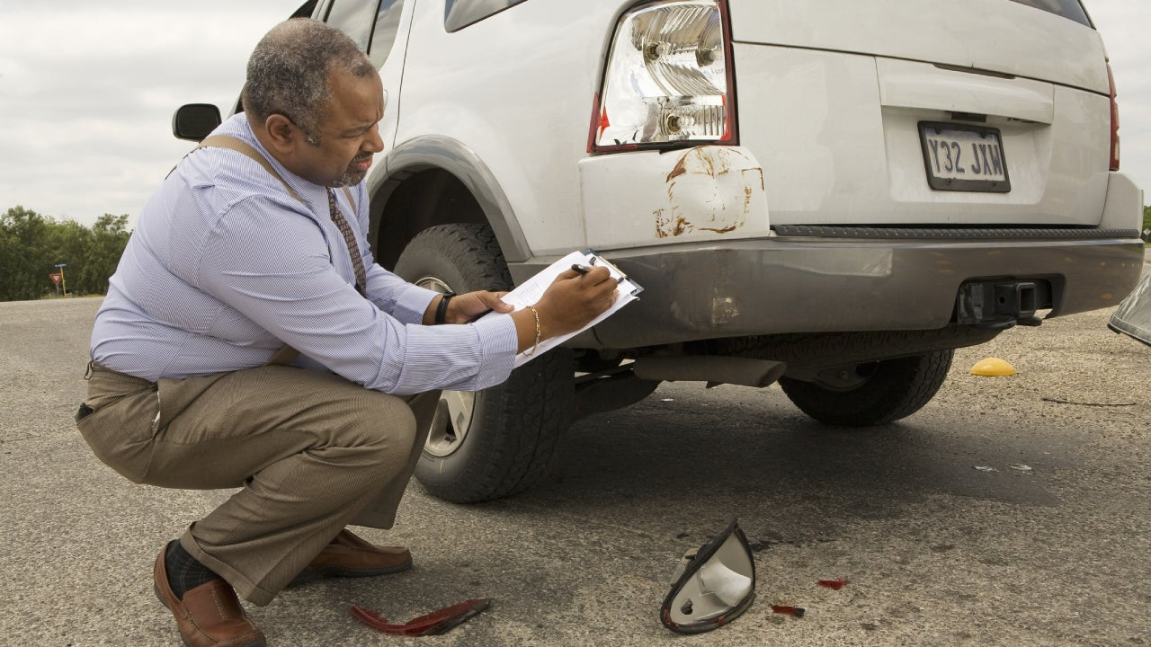 An older African American man assessing the damage to the back taillight of a car.