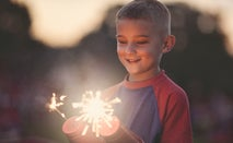 A boy holds two sparklers and stares at them in wonder (his hands are protected by two red, plastic cups where holes have been poked in them to hold the sparkler sticks)