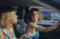 Two young ladies laughing while sitting in the car together.