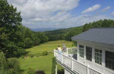 People standing on the deck of their home in Vermont, staring out at the wide, blue sky.