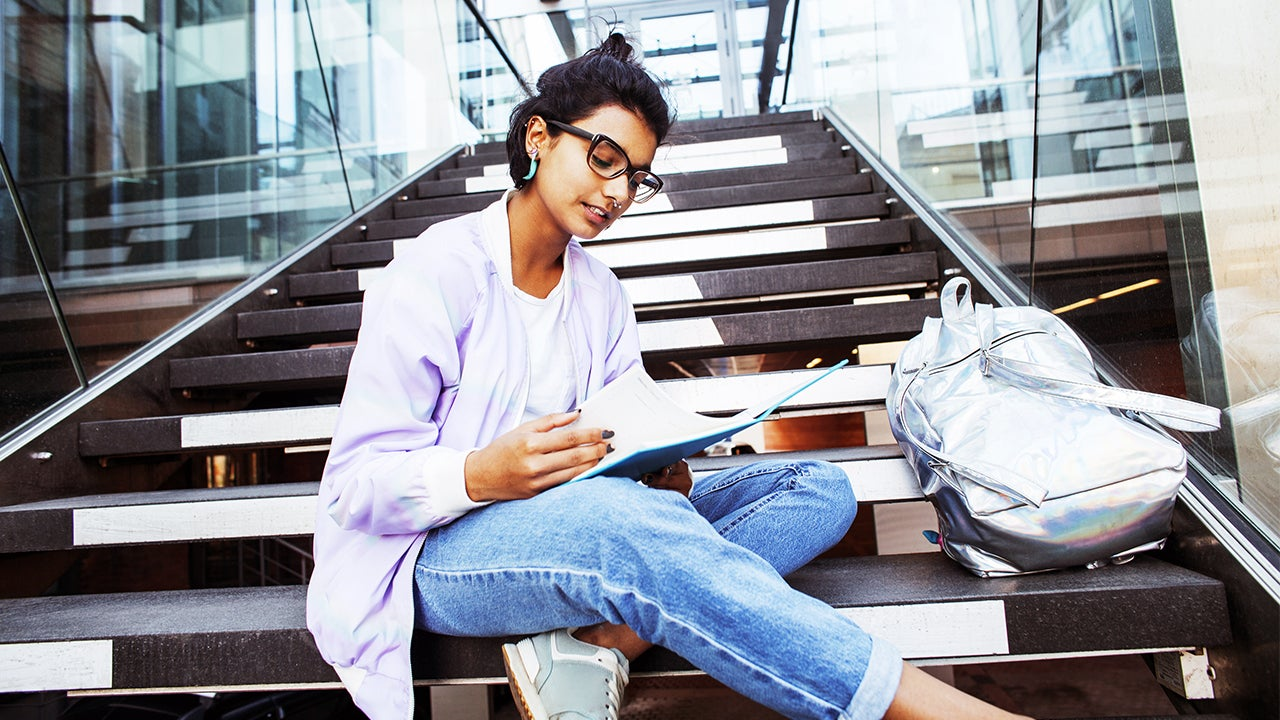 College student sits on steps while studying.