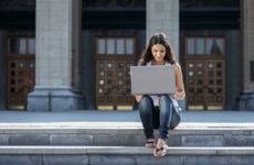 Student sitting on campus steps working on laptop.