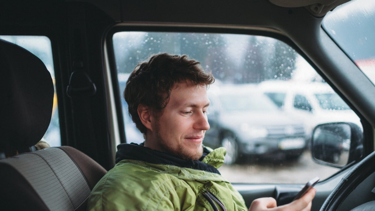 A young man in a green jacket sits in his car, staring down at his phone.