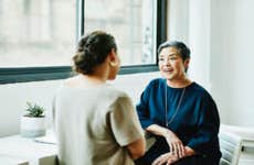 Smiling businesswoman in discussion with client in office conference room