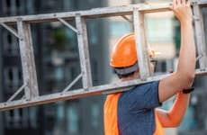 A man carries a ladder.