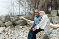An older couple sitting together on a rocky beach.