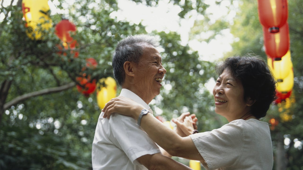 An older Asian couple dancing outdoors at a festival and laughing together.