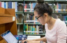 College student studies in library.