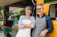 An older White couple stands with aprons in front of a food truck