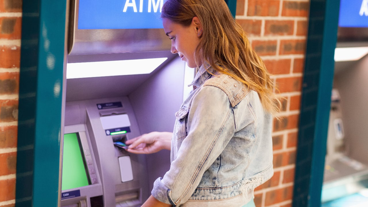 A student withdraws cash at an ATM.