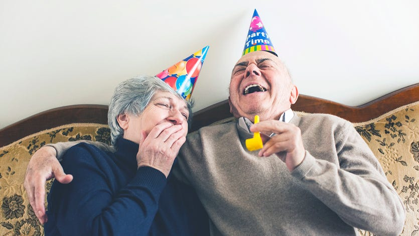An older couple laughs with birthday hats on