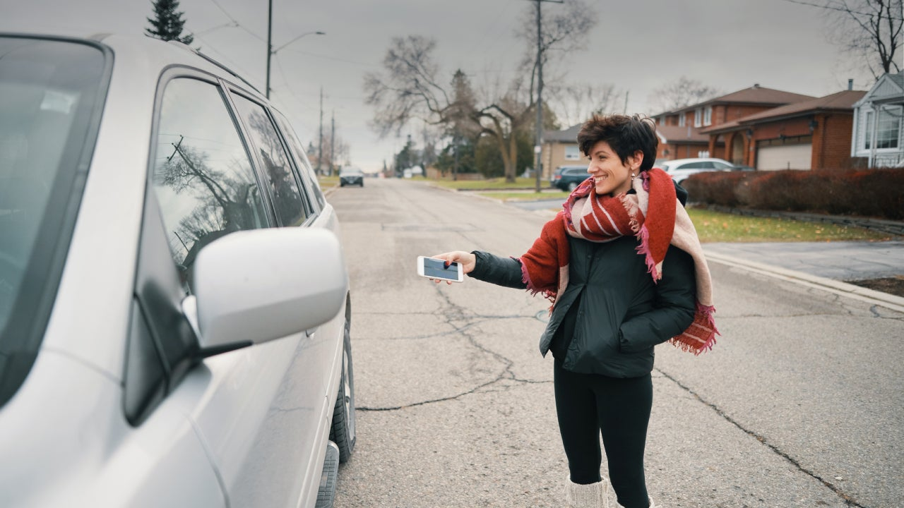 A woman stands outside of her smart car and activates it using her smartphone.