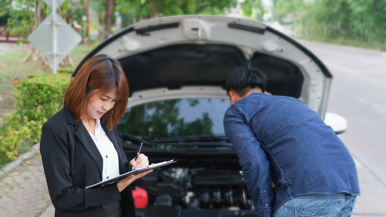 An insurance adjuster looks over her clipboard next to a broken down car while the driver examines under the hood.