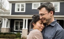 A man and woman embrace in front of their home.