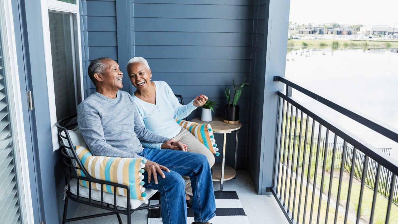 Two seniors enjoy sitting outside their home