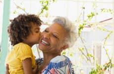 A young Black girls kisses her older Black relative