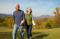 An older couple walks in a field