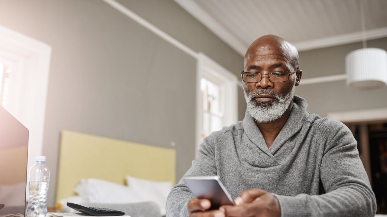 An older black man sits at his table with his phone and a list of finance reports to review.