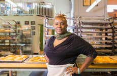 An older Black businesswoman stands in front of her kitchen