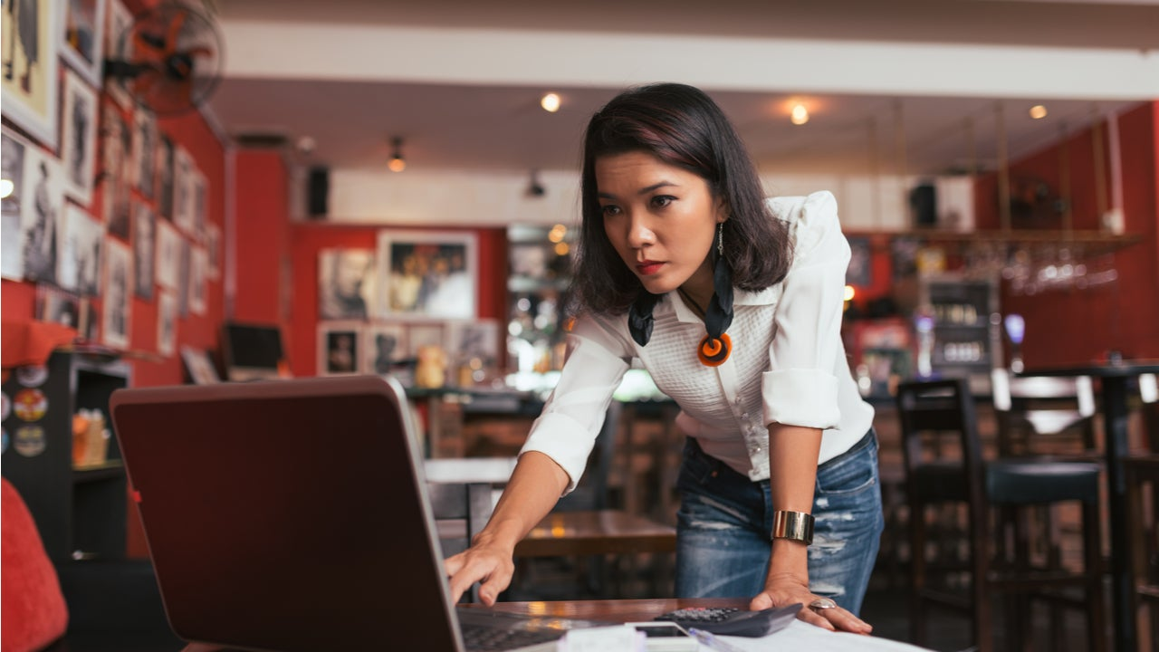 Concerned woman looks at laptop.