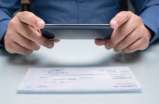 A man takes a picture of a check.