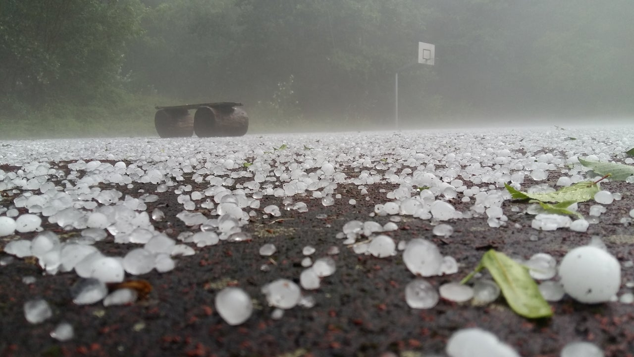 Close-up shot of golf-ball-sized hail stones on the ground.