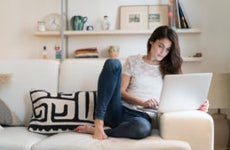 Woman sitting on couch at home using laptop