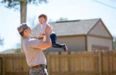 Young male soldier holding up toddler daughter in garden at air force military base